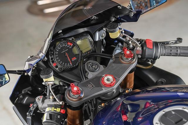 画像: ミラーはカウル前側からカウルステーに取り出し位置を変更、カーボンモノコックボディのミラーはマジカルレーシング製で、カーボントリム付きのスクリーンも同じくマジカルレーシング。クラッチ側駆動はワイヤ式から油圧化され、ブレンボマスターを装着する。