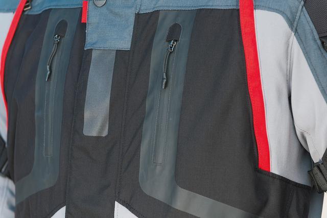 画像: フロントの大口径ポケットには止水ファスナーを採用。フリップ付きでグローブのまま開閉できる。