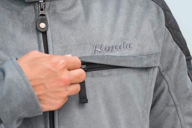 画像: 胸元には控えめなHondaの刺繍ロゴ。胸ポケットはフラップとファスナー付きとなっている。