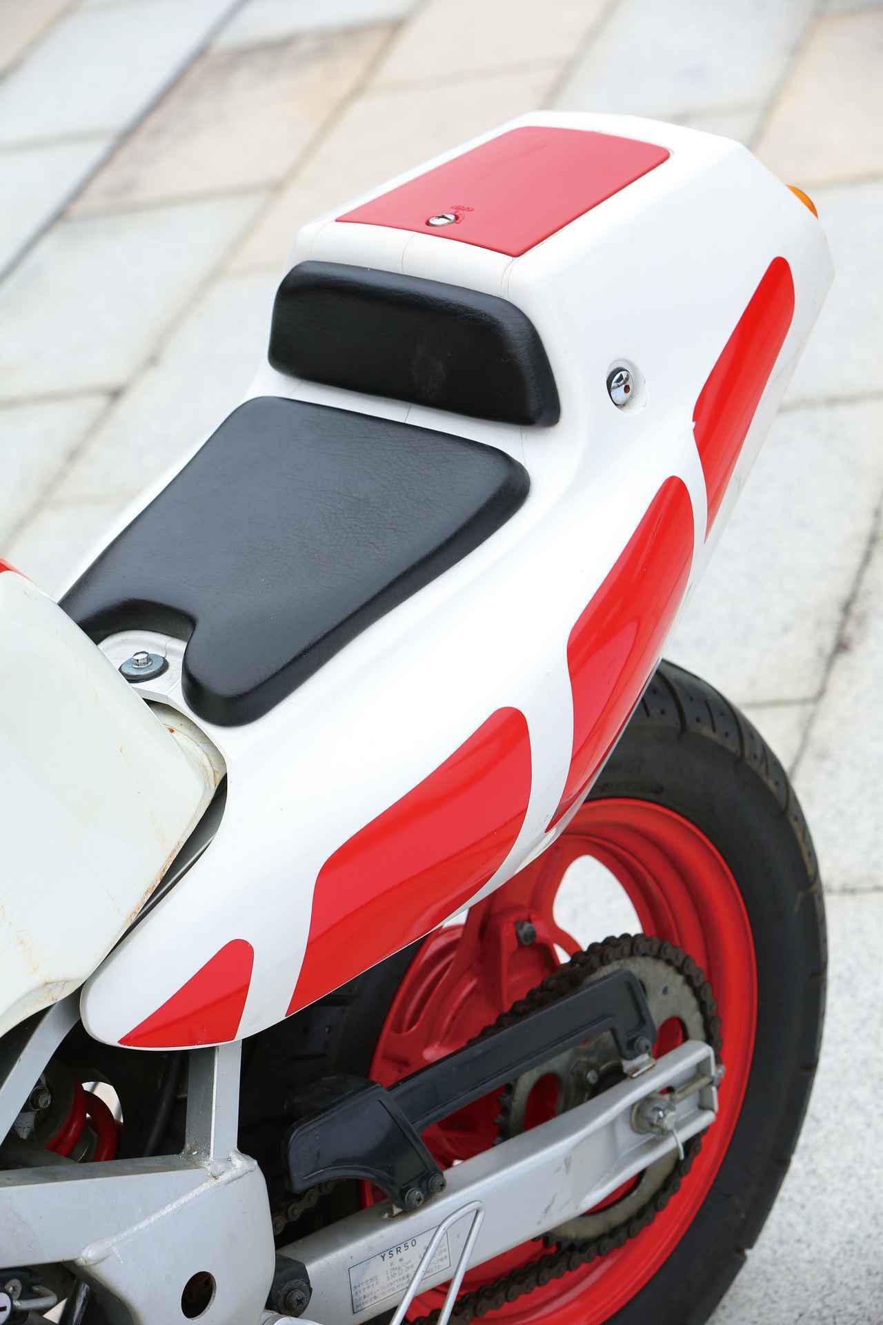 画像: 有機的でグラマラスなボディラインが美しいシングルシートカウル。後方上部のフタの中は小物入れになっている。兄貴のYSR80と違い50では泥除けが装備されていないのが特徴だ。