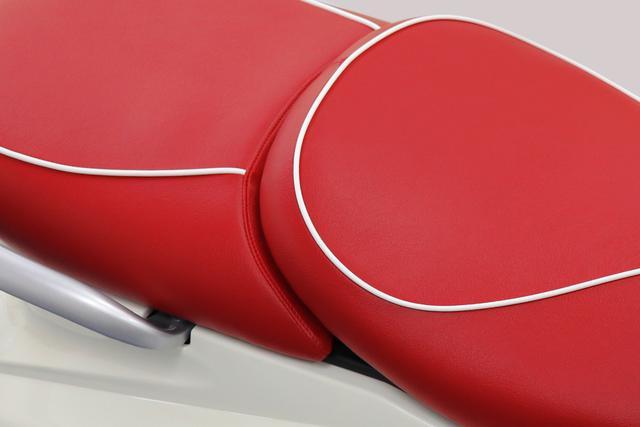 画像: 鮮やかな赤の表皮に爽やかな白いパイピングを施した、専用カラーのシートを装備。従来モデルと比べライダーの着座位置を約2cm低くし、良好な足つき性を実現しています。バイクビギナーでも安心して乗れる嬉しい配慮ですね。