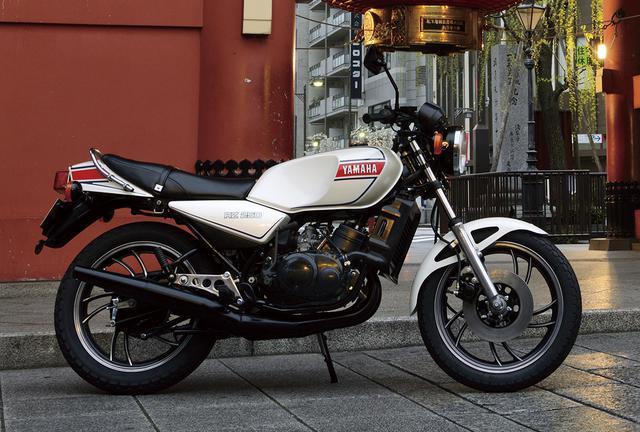 画像: ヤマハ RZ250 82年のバイクブームは突然訪れたわけではない。中型免許がメインの若いライダーを惹き付けるニューマシンが、80年から続々と登場していた。その1台が2ストを復権させ、その後の250レプリカブームの嚆矢となったRZ250だ。そのデビューは、それまでバイクに興味のない者をライダーに誘うほどのインパクトを持っていた。 【RZ250主要諸元】●エンジン形式:水冷2スト・ピストンリードバルブ並列2気筒●総排気量:247cc●最高出力:35PS/8500rpm●最大トルク:3.0kg-m/8000rpm●乾燥重量:139kg●燃料タンク容量:16ℓ●タイヤサイズ前・後:3.00-18・3.50-18●発売年月:1980年8月●発売当時の新車価格:35万4000円