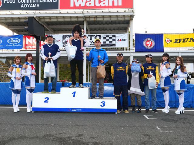 画像: 左から2位・池田秀一選手、1位・冨永崇史選手、3位・廣瀬 章選手、4位・作田隆義選手、5位・大越研二選手、6位・中嶋秀和選手。表彰式には岡山国際サーキットのサーキットクイーンも華を添えてくれた。