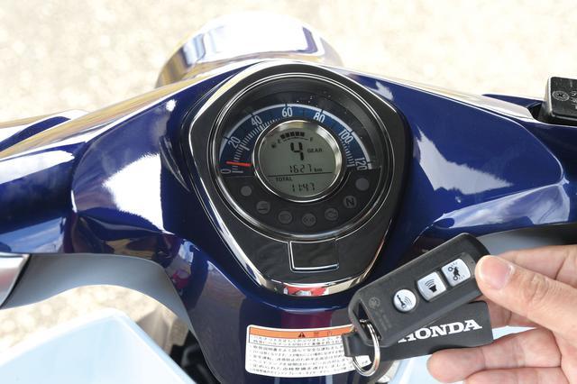 画像: 外側がアナログ表示、内側がデジタル表示という、視認性に優れるスーパーカブC125のメーター。外枠はクロームメッキで、高級感を巧みに演出。スマートキーにはオールドタイプのウイングマーク付き。