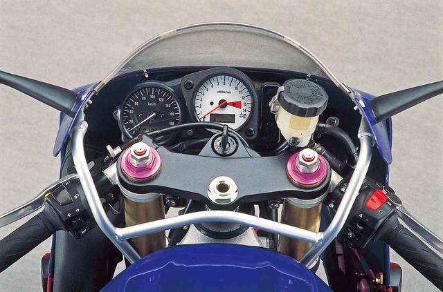 画像: メーターは速度計も電気式となり、前輪ハブのギアとケーブルを消滅させて重量を削減。14000rpmが上限、12000rpmからをレッドゾーンとする回転計の文字盤に水温計を配置した結果、これまでの3連から2連に変化。左側に置かれるスピードメーターの文字盤は黒で液晶のオド/トリップを装備。ウィンカーやハイビーム、ニュートラルなどのインジケーターランプは右端に縦に並べられる。フロントフォークの上部キャップはこの色が標準で、中央部でプリロードと伸び側減衰力を調整できる。