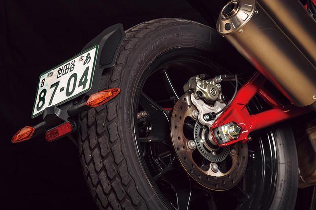 画像: リアフェンダーはスイングアームに片持ちマウントする形状で、ナンバープレートとウインカーも装着される。リアブレーキはブレンボ製2ピストンキャリパーと、265mmローターを組み合わせる。ホイールサイズはフロント19・リア18インチ。装着されているタイヤは、FTR1200シリーズ用にダンロップと協力し、フラットトラックレース用タイヤ・DT3をベースに開発されたというDT3-R。
