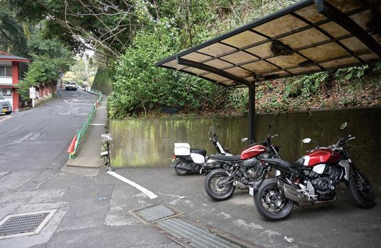 画像: 鳥居を正面に、右側の坂を入ると二輪用スペースが。バイクの出し入れに優しいフラットな場所で、屋根付きの配慮もありがたいですね。