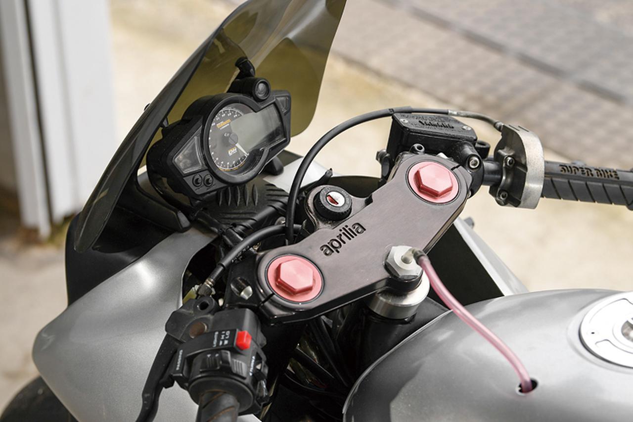 画像: フロントフォークまわりに合わせて、ステムまわりもアプリリアから流用したという。液晶パネル+アナログ回転計ワンボディのメーターはSP武川製を装着。