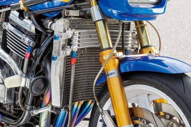 画像: 冷却系はラジエーターを大型化した上でその前にオイルクーラーを重ねてマウント。上下配置で気になるタイヤへの干渉も抑えつつ、一番走行風の当たる箇所にオイルクーラーを置くことで冷却効果も損ねずに済む方法だ。マウントステーもオリジナルで製作されている。