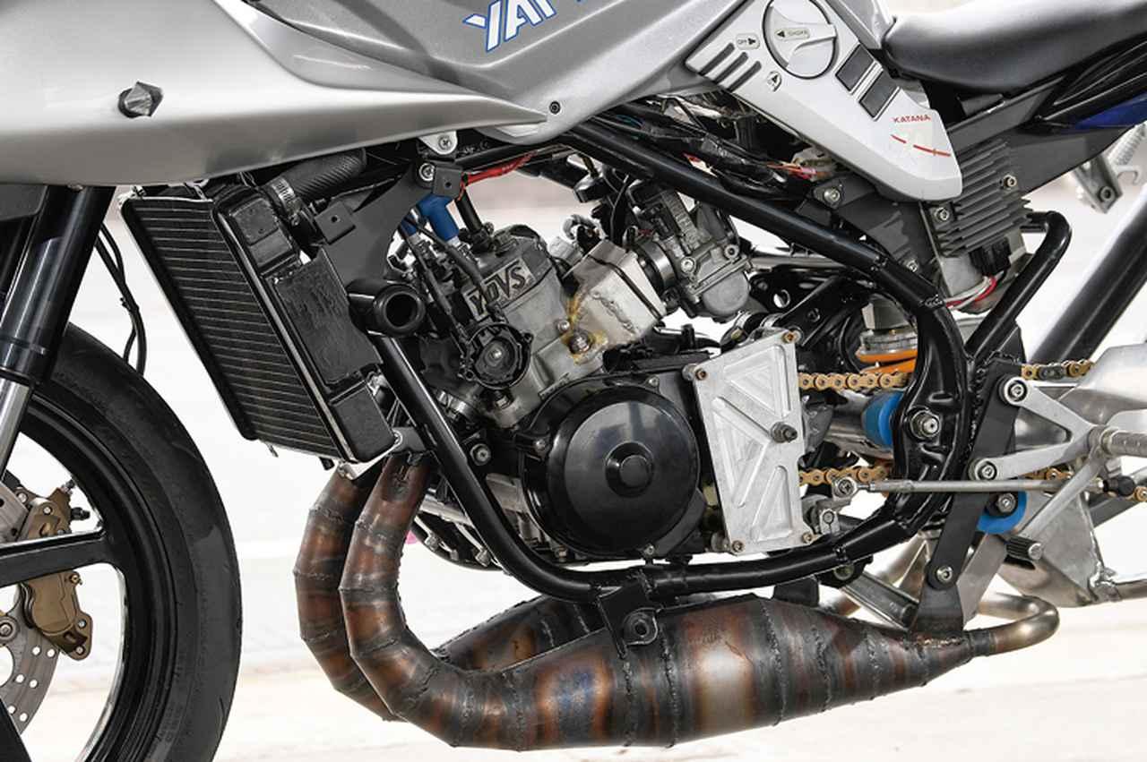 画像: エンジンはRZ250Rの並列2気筒をピストンリードバルブからセミクランクケースリードバルブ式に加工済み。シリンダーも補助排気ポートを追加工、これに応じてピストンはNSR250RのMC21用加工流用している。点火系はOSR・CDI電撃スペシャルで、キャブレターにはケーヒン製PJ38ショートをチョイスした。