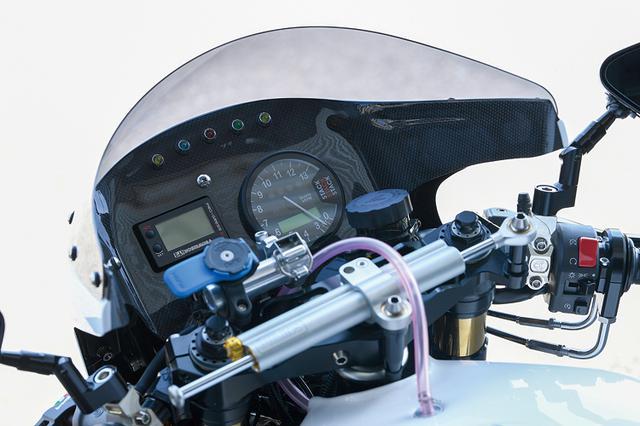 画像: メーターはインナーパネルをカーボンで製作しSTACK多機能メーター(右)、ヨシムラ・プログレスデジタルメーター(左)をセットする。左右マスターシリンダーはブレンボでカーボンモノコックミラーはマジカルレーシング。オーリンズステアリングダンパーもマウントしている。