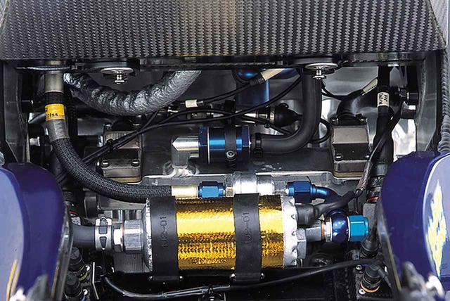 画像: クランクケース(ミッション室)上部には、後方(写真手前)から順に、断熱材を巻いたうえで2本のゴムバンドで取り付けられたフューエルインジェクション用の電磁ポンプ、それと配管でつながったフューエルフィルター、負圧パイプの後端を連結した負圧チャンバー(2003年モデルまではフレームのクロスメンバーを兼用していたが、2004年型では独立したアルミの角箱になった)と吸気エアボックス(スロットルボディを収納)を結ぶ配管、そしてその前方に、クランク室下部から伸びるホースの先端にマウントされた油圧センサーが見える。