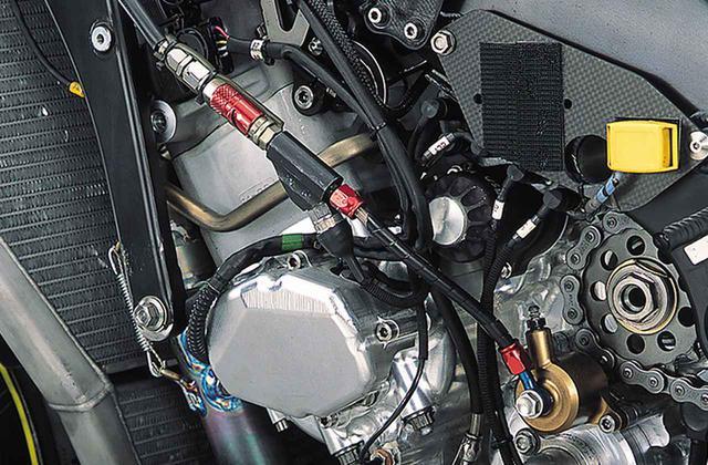 画像: クラッチの油圧レリーズホースの途中には3ウェイがあり、分岐の先に圧力センサーを取り付け、クラッチ操作を検出している。4サイクルのレーシングマシーンに必須のエンジンブレーキ緩和システムもまた大きく進化した。ライダーがスロットルグリップを戻してもスロットルバルブが全閉にならないシステムを採用することにより、従来のクラッチを滑らすメカニズムを廃止。耐久性と安定性を高めた。