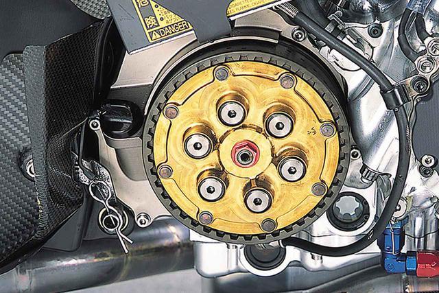 画像: 窒化チタンコーティングされた金色のプレッシャープレートが目立つクラッチ。その奥のミッション室カバーは、マグネシウムの削り出しにカニゼンメッキ(無電解ニッケルメッキ)を施したものである。アルミ削り出しパーツの増加で、YZR500と比べてマグネシウムパーツの数は少なくなっている。エンジンオイルの点検窓は、クランクケース側とオイルパン側に1個ずつあり、両者の中間(上にオイルが見えず、下に空気が見えない)が基準と思われる。