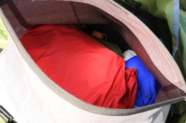 画像: このうち、レインスーツはメイン気室の一番上に配置。雨が降ってきたときに荷物をひっくり返すのは嫌ですからね。バッグの後ろに備わっているポーチには、マルチツールやヘッドライト、使い捨てカイロ、ウエットティッシュを入れていました。