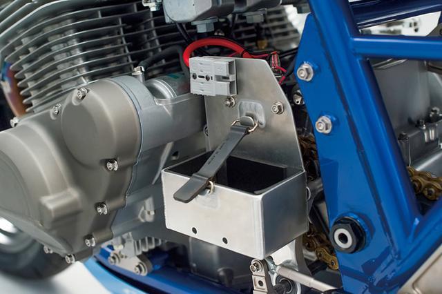 画像: 夜間走行でのヘッドライト使用時にはバッテリーボックスとなるアルミケースをエンジン左に追加。上のボックスにバッテリーと+-端子がワンタッチではまり、ヘッドライトユニットも同様にフロントゼッケン部に装着されて点灯する(装着したままの場合もある)。昼間のレースでの軽量化と夜間照明を両立するものだ。