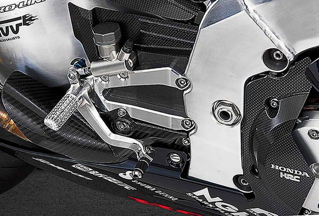 画像: やや前寄りから見た右側ステップまわり。クラッチのカバー/シートのステー部分/上下2枚のマフラーのガード/マスターシリンダー裏のガード/ステップ裏のプレートなど、多くのカーボンパーツが集まっているが、それぞれ織り目や製法は異なっている。ステップブラケットやマスターシリンダーの取り付けボルト/アンダーカウルやシートの取り付けボルトやファスナーなどは、いずれも面に落とし込み、徹底したフラッシュサーフェス化を図っている。スイングアームピボット部のフレーム部材は、裏側にポケット加工を施した削り出しパーツであり、上部の斜面にボールエンドミルによる切削痕が見える。