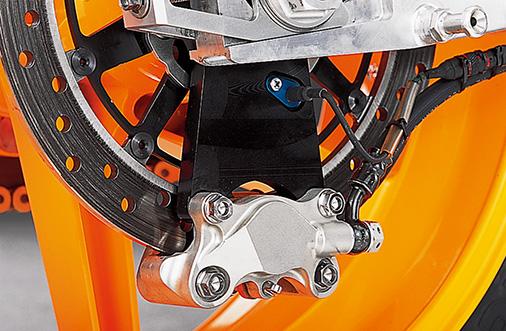 画像: リアブレーキは、フローティングマウントのステンレスディスクとシンプルな対向2ピストンキャリパーの組み合わせ。リアとしては直径の大きなディスクを使用するのはヘイデンの好みに合わせた仕様。キャリパーブラケットはチェーンプラーにマウントされており、トルクロッドは持たない。このブラケットを貫通して車速センサーがマウントされ、ディスク内周のプレートの切り欠きをカウントする。