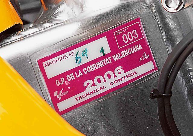 画像: ステアリングヘッド右脇のフレームに張られた車検(テクニカル・コントロール)ステッカー。2006年最終戦・バレンシアGPでヘイデンが優勝(と同時にタイトル獲得)を飾ったマシーンそのものの証明だ。