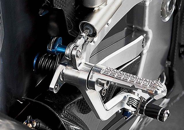 画像: リザーバータンクを一体で削り出したリアマスターシリンダーをマウントする右側ステップブラケット。ブレーキペダルはステップと同軸で、裏側にリターン用の強力なコイルスプリングが見える。このスプリングの位置決めピンの凝った造りに注目。マスターシリンダー裏側とステップ下側には立体成型されたドライカーボンのガードを装着。