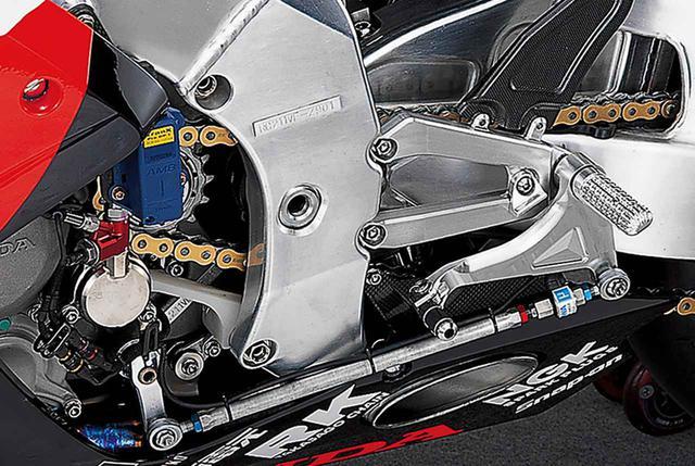画像: 左側ステップまわりで特徴的なのは、長いロッドを介してシフトアームと連結されたシフトペダル。厚めの材料を用いて、肉抜きも貫通とせずポケット加工に留め、剛性を確保している。金色アルマイト処理のクラッチレリーズシリンダーには、油圧センサーをマウントする。その上の青いパーツは、ラップタイム計測用のトラックセンサーだ。
