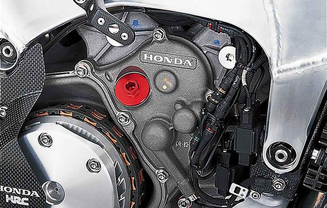 """画像: クランクシャフト〜ミッションのメインシャフト間の距離を詰めて、配置を変更した""""ニュージェネレーション""""エンジンの特徴が表れた、右側クランクケースカバー前方上部。従来型ではクラッチ前方下部に配されていたエンジンオイルのフィラーキャップ(赤色アルマイトのパーツ)は、軸配置の変更とクランクケースの小型化によって、ここに移された。クランク軸中心は黄色のペイントよりも下寄りにある。"""