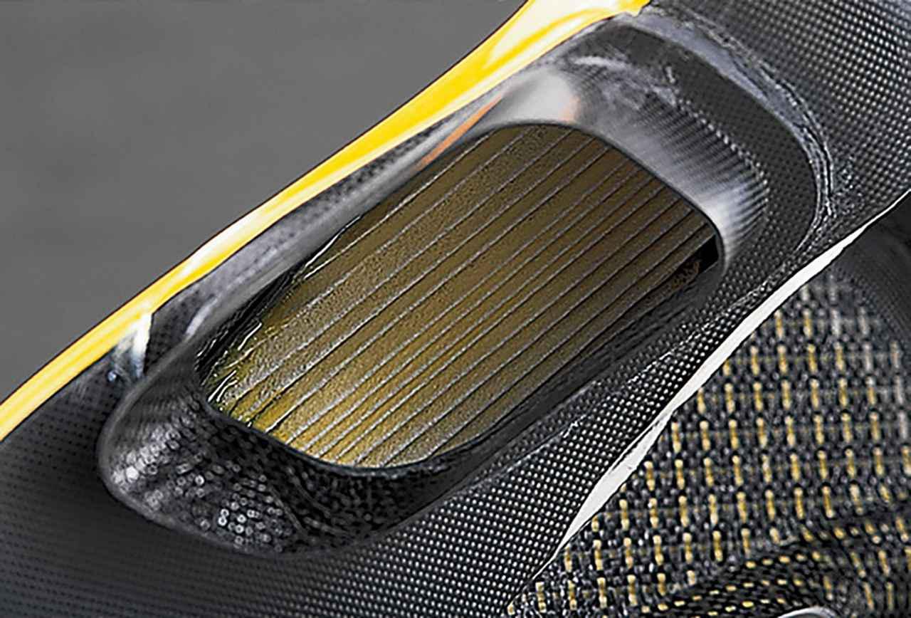 画像: サイドカウル内側のダクトの、メインフレーム側面の穴にはまり込む部分のアップ。サイドカウル本体は、剛性の高さよりも破断に対する強度を上げるため、ドライカーボンではなくカーボン+ケブラー繊維による強化樹脂製であり、その裏面にドライカーボンのダクトを取り付けたうえ、別に成型されたカーボンFRP製のジョイント部を張り付ける。ダクトの内側にはろ紙式のエアクリーナーが装着されている。交換の際はこの部分をアッセンブリで取り替える。