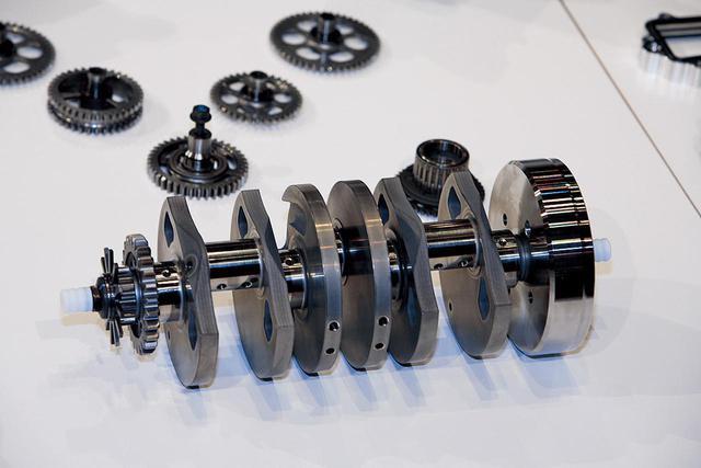 画像: V型5気筒エンジンならではの特徴が表れたクランクシャフト。2本のコンロッドを装着する左右のクランクピンは長いが、1本のみの中央は短い。右にジェネレーターのローター、左端には内側から順にプライマリードライブギア/カムドライブギア/ピックアップローターがマウントされている。背後に写っているのは、カムシャフト駆動用のギアトレインを構成するギアである。