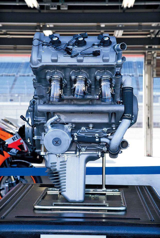 """画像: New Generation(RC211V -2006-) 徹底して小型・軽量化したとは聞いていても、カウリングを外しただけでは、このアングルからエンジンを観察することはできないので、まさかここまで小さくなっているとは思わなかった。ボア×ストロークは非公開だが(2種のエンジンが異なる可能性を示唆した発言はあった)、少々ボアを縮小しただけでは、ここまで気筒ピッチは詰まらないし、出力向上を達成したことと、より高回転化したいだろう来季用800㏄エンジンへのつながりを考えると、ショートストローク化のためにボアを広げたうえで、気筒間隔壁を限界まで詰めた可能性はある。このあたりが""""耐久性に関する余裕を落とした""""部分なのかもしれない。位置や向きも異なる水冷式オイルクーラー/その左側(写真では右)のクランクケースに収納されたオイルフィルターのカバー/フィンを設けたオイルパンの形状/大径・薄型になった左側クランクケースカバーなども、完全な新設計を証明。"""