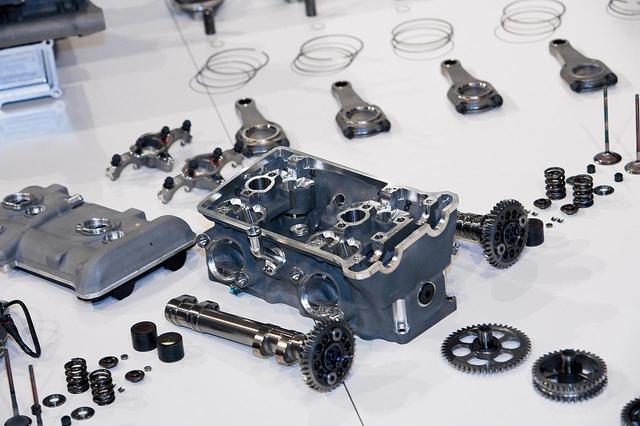 画像: 後ろ側のシリンダーヘッドは、その周囲にカムシャフト/ドライブギア/バルブまわりの小物パーツを並べて展示されていた。バルブ駆動は、コイルスプリング+インナーシムを持つバケットによる直押しタイプであり、方式は一般的だが、材料/加工/管理などには、最先端技術が使われているはずだ。