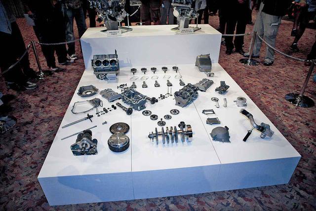 """画像: 2種類のエンジン単体を壇上に、分解した""""ニュージェネレーション""""エンジンの各パーツを卓上に並べた、RC211Vエンジン世界初公開の風景である。"""