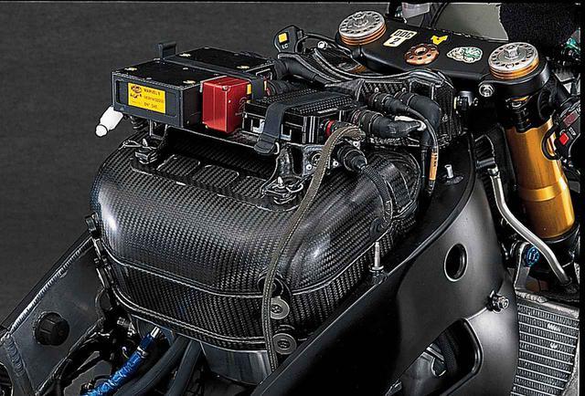 画像: 2004年型まではフロントカウル内部に集中していた電装系パーツの多くは、2005年型から吸気エアボックス上部に移された。アルミの底/ドライカーボンの胴/ドライカーボンのフタという3層構造のエアボックスの上に電装系取り付けベースがあり、その上に、左から順にイタリア・マレリ製のフューエルインジェクション用ECU、目的不明の2Dのパーツ、スロットル制御用ECUとおぼしきブラックボックスが並んでいる。そのさらに前方、ステアリングのトップブリッジ直後にカバーがあり、メインの点火系ECUなどはこの中にあると思われる。