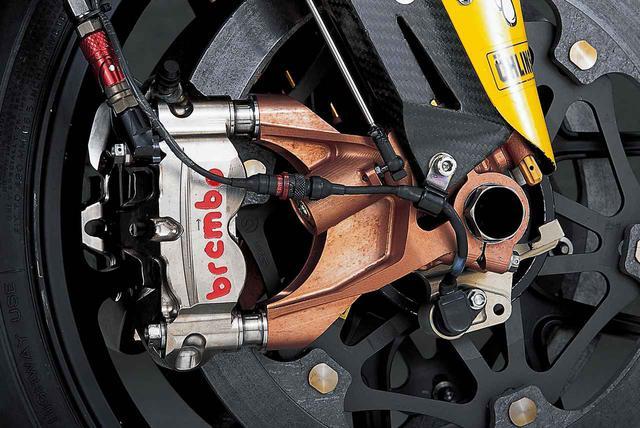 画像: オーリンズの倒立型・フルアジャスタブルフロントフォーク/マルケジーニのマグネシウム鍛造ホイール/ミシュランのレーシングラジアルタイヤ/ブレンボのφ320㎜カーボンコンポジットディスク/ブレンボのモノブロック・ラジアルマウントキャリパーで構成されたフロントまわり。必要最小限の厚さを残して肉抜きされたアクスルの薄さに注目。左側にも車速センサー(ホイールの回転を検出)があるが、なぜ両側に必要なのかは不明。キャリパーのメインテナンスを容易にするため、ブレーキホースの途中にクイックジョイントを設けている。