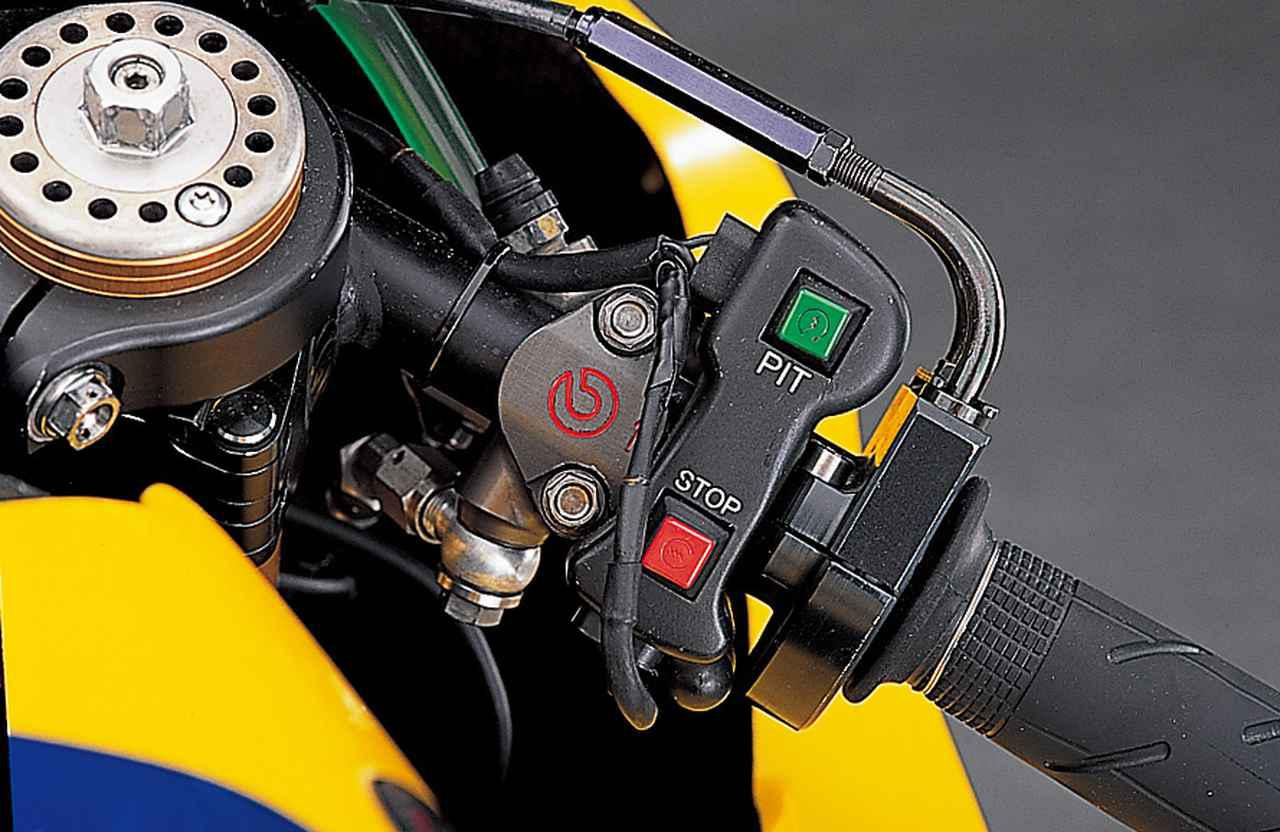 画像: 右側グリップ基部にあるPITと書かれた緑のボタンは、ピットレーン走行時のスピードリミッターのスイッチ。プラクティス中のピットイン/ピットアウト時に制限速度を超えると、決勝結果に対してペナルティを課されるため、それを防止するのが狙い。その下の赤いボタンは通常のエンジン停止用である。