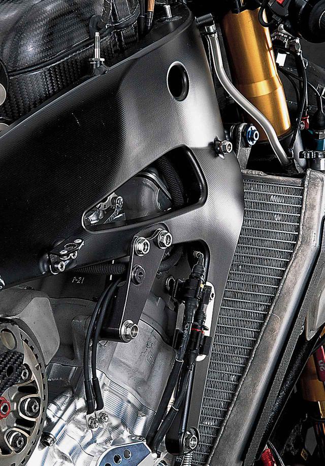 画像: V型エンジンと比べると幅の広い並列4気筒のシリンダーヘッドを取り囲むような形状のフレーム。前側のエンジンマウントは2カ所で、フレームと一体のエンジンハンガーがクランクケース前部に、エンジンハンガー〜メインフレーム間のステー部分(これも一体)の途中にボルト留めされたブラケットがシリンダー背後に取り付けられている。フレーム表面に走る無数の切削痕に注目。このマシーンのフレーム部材はほとんど削り出しパーツで、それらを溶接して構成している。