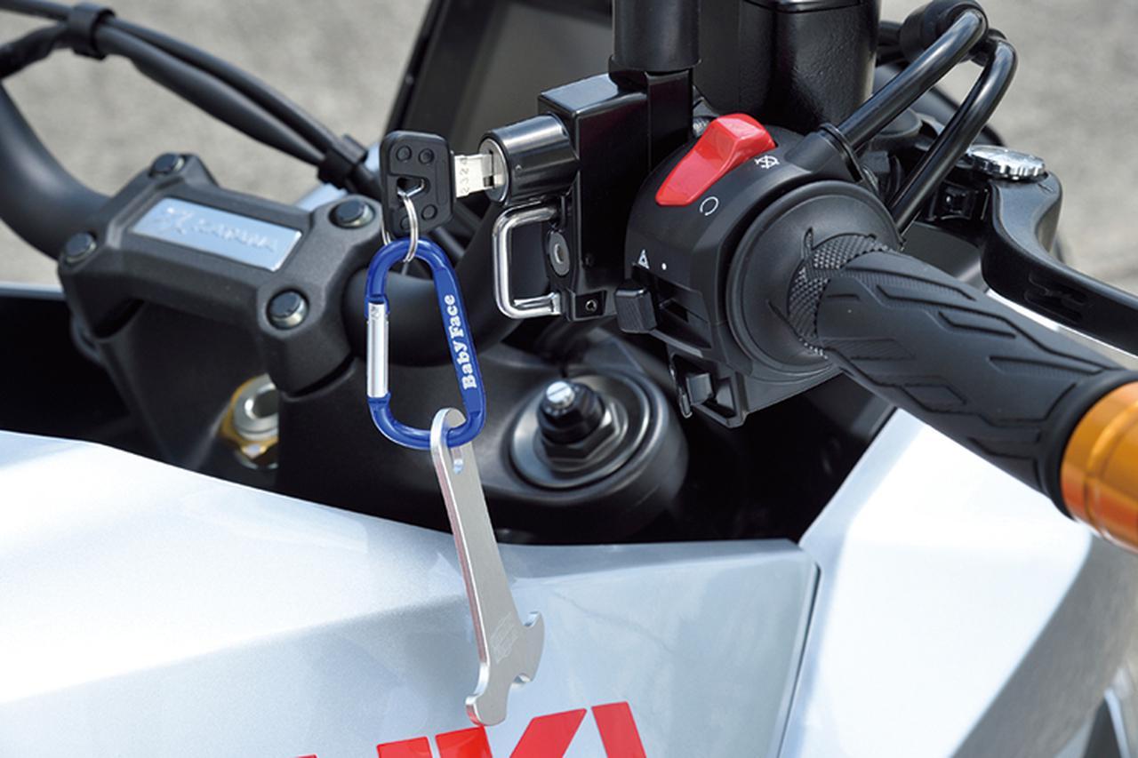 画像: 「ヘルメットロック ミラーホルダータイプ 32㎜」(7000円+税)はフロントマスター部またはクラッチ側に装着するアイテム。カラビナとその下のパーツはヘルメットのDリングに挿入しホルダーに付けやすくするアンカー(1500円+税)だ。