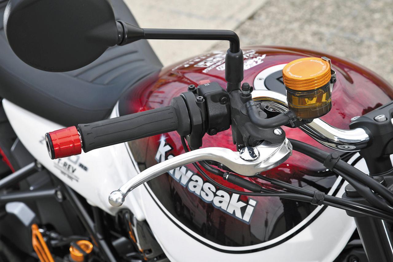 画像: ブレーキマスターシリンダー(ここでは純正のNISSINラジアルポンプ)の別体リザーブタンクキャップ(NISSIN-φ52)は税別5500円。リヤ用もあり税別4000円(NISSIN-φ38)。 バーエンドにはさまざまな形状やカラーが用意されているが、ここで装着されるのはφ35mmアルミ合金アルマイト・レッド。バーエンドがレッド、外からエンドを止めるピースはブラックのジュラコン製でベビーフェイスロゴも入る。