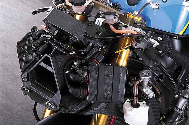 画像: 略三角形断面のダクトはステアリングヘッド部でフレームに固定されており、メーターや電装パーツのステーにもなっている。ダクトを通る空気は、ステアリングシャフトを避けて両脇に分流し、フレームを貫通して吸気エアボックスに向かう。こちら側のエアシュラウドに取り付けられた樹脂製のタンクはラジエターのリカバリー用。ブリーザーは、後方に伸びるもう1本のチューブで下向きに大気開放される。