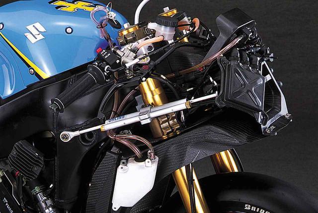 画像: ステアリングダンパーはオーリンズ製の油圧式で、前方に効力調整ダイアルを持つ。フロントフォークのロアブラケットは左右各2本のボルトで締めつけられる。トップブリッジとは微妙に色合いが異なるが、こちらもマグネシウム製かもしれない。ラジエターとダクトを結ぶカーボンFRP製のエアシュラウドに取り付けられた白い樹脂製タンクには、フューエルタンクにつながるブリーザーチューブが差し込まれており、前方のニップルから上に伸びる配管からラム圧を導き、吸気エアボックス内とフューエルタンク内の圧力差を補正している(補正しないとフューエルタンク内がエアボックス内よりも低圧となり、最悪の場合、インジェクターへのガソリンの供給に支障が出る)。