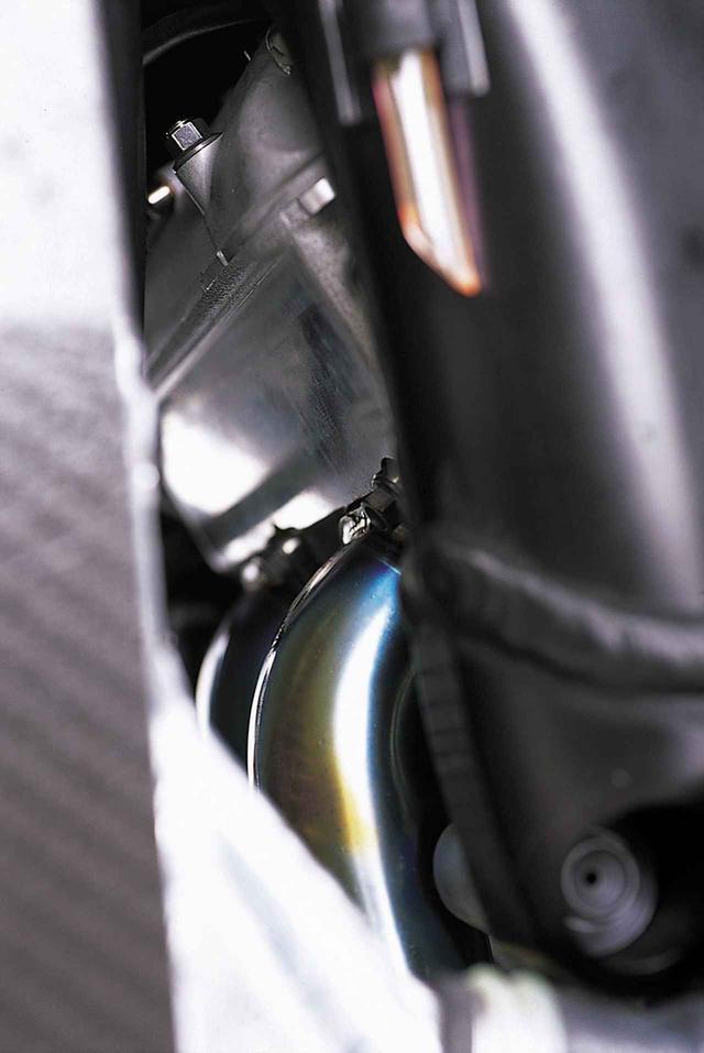画像: エンジンハンガーとラジエターの間のわずかなすきまから見たシリンダーヘッドとヘッドカバー。どちらもアルミ鋳造パーツである。
