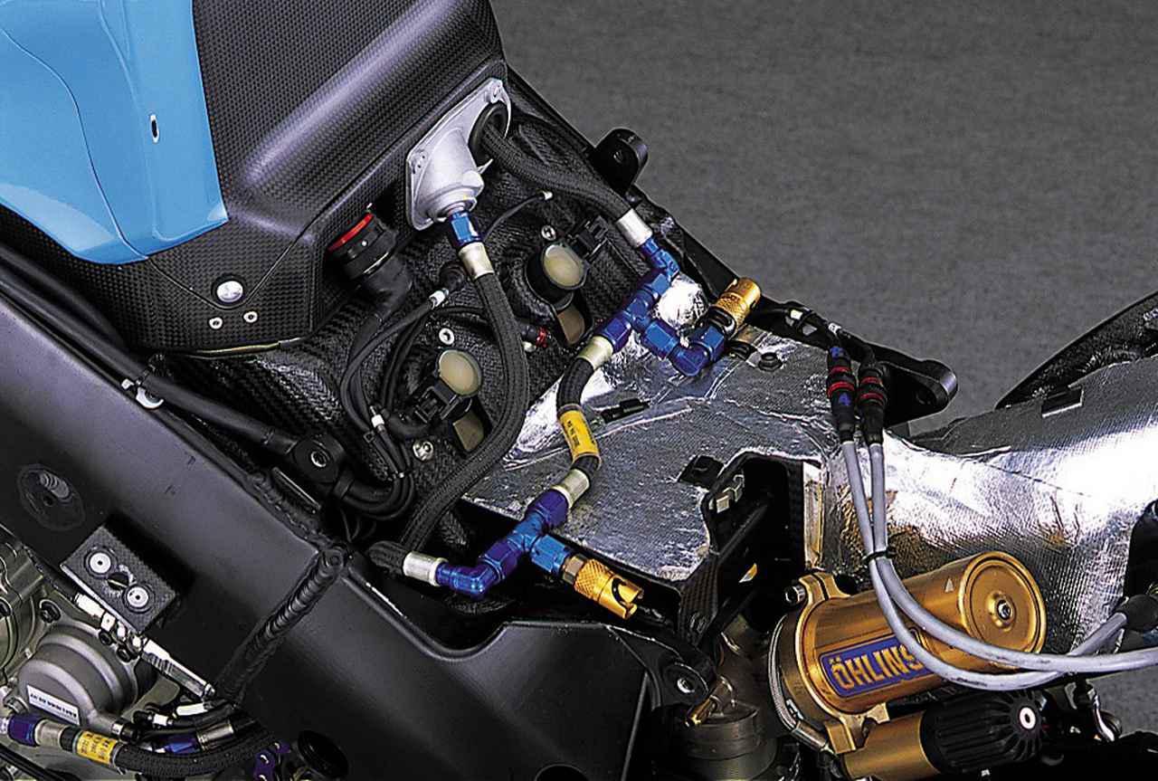 画像: フューエルタンクを外すと、後ろ側バンクのシリンダーヘッド上部が見える。白っぽい樹脂を封入した2個の円筒形がダイレクトイグニッション(各気筒のスパークプラグにイグニッションコイルを直付けした方式)のコイルの一部であり、これにより、おおよそのシリンダー間隔がわかる。青アルマイトのアルミ製フィッティングパーツを多用した配管は、フューエルタンク〜ポンプ〜インジェクターを結ぶ燃料ライン。ジョイントにはクイックリリースタイプを使用している。