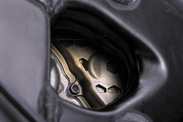 画像: フレーム右側面の穴の内部は、レクチファイア/ボルテージレギュレーターが邪魔をして見づらいが、わずかに見えるシリンダーヘッド/ヘッドカバーの形状により、右側にカムシャフトのドライブトレインがあることがわかる。さらに、シリンダーヘッド/ヘッドカバーの合わせ面が気筒中心線に対して傾いて(前下がりになって)いることから、吸気ポートをできるだけ直線的にするために、排気側カムシャフトよりも吸気側カムシャフトを高い位置に置いていると推察できる。