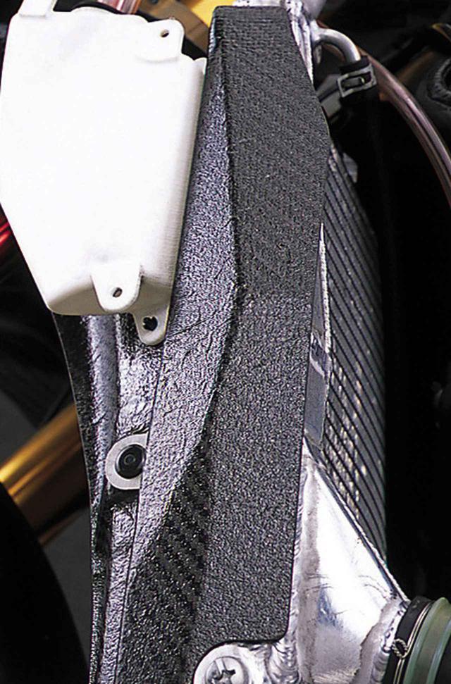 画像: 限られたスペースの中で放熱効果を高めるためにラウンド形状のラジエターを使うのは、今やレーシングマシーンの常識となっている。そのうえで、少しでも多く前輪分布荷重を稼ぐべく、シリンダーヘッドとラジエターのすきまをギリギリまで詰めたマシーンが多いのに対し、GSV-Rは比較的余裕がある。前輪分布荷重の増大よりも、排気ポート直後のエキパイの曲がりを緩やかにするのを優先した結果か。
