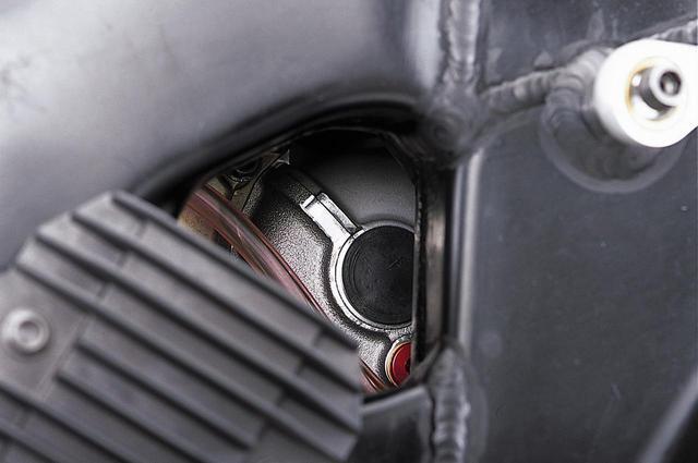 画像: エンジン右側前方の眺めは複雑だ。ラジエターの下にあるオイルクーラーへの配管は、カートリッジ式オイルフィルターの基部から出ており、オイルポンプからクランクケース内を通って圧送されたオイルは、まずオイルクーラーに入り、そこから戻った後にフィルターを通過してエンジン各部に向かっているものと思われる。注目すべきは、2本のエグゾーストパイプに取り付けられたO2センサーからの信号線カプラーの上部にある黒いプラグ(上下2本のボルトで固定)だ。何らかの軸加工をした跡なのは明らかで、ちょうどクランクケースの上下分割面にあり、ここを中心とする円形の張り出しが見えることから、こちら側にもバランサーが存在するのではないかと想像できる。
