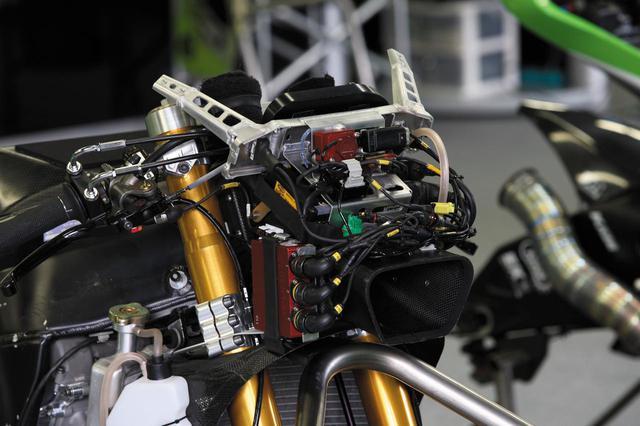 画像: ステアリングヘッドパイプの両脇を通って吸気エアボックスに達するダクトの上に、フロントカウル/メーター/電装系パーツのための兼用ステーがある。3本の太いコネクターがつながった赤い箱はデータロガー、その上に見える黄色いラベルを張った黒い箱はマレリ製のフューエルインジェクションのコントロールユニットと思われる。