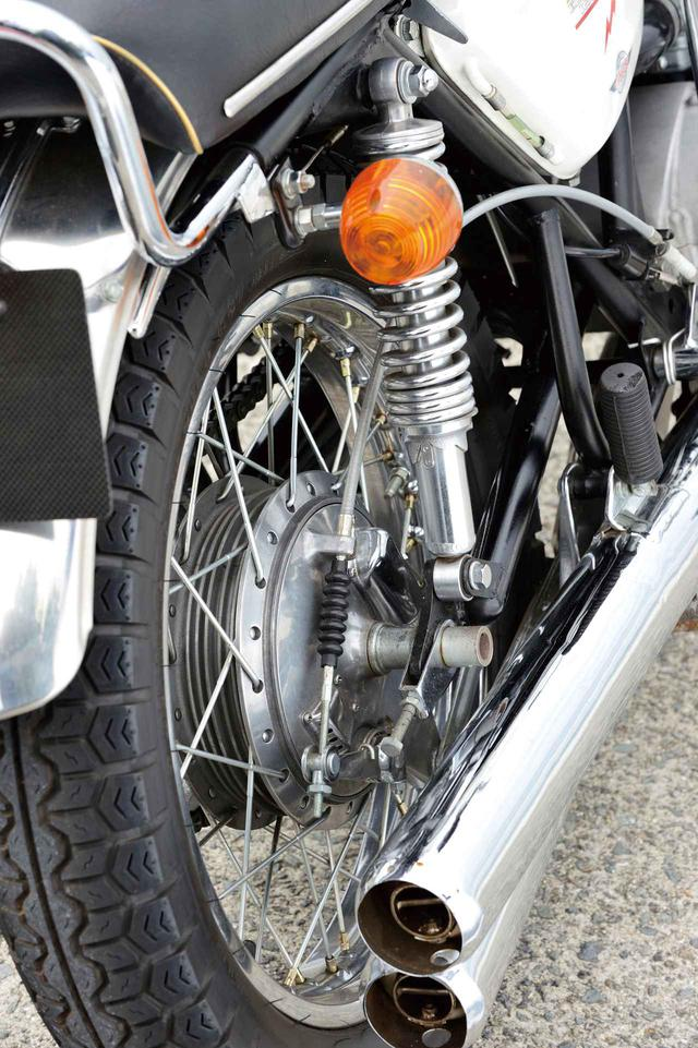 画像: 鉄パイプのスイングアームにオーソドックスな2本サス。φ180㎜のドラムブレーキはフロントと同じワイヤー式で、タイヤは専用のK77を装着する。