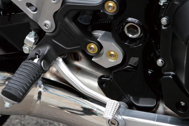 画像: ノーマルステッププレートの下部マウント部分にアルミ削り出し品を入れ、ステップ位置を後方/上方へ。プレートカバーもワークススポーツオリジナル。