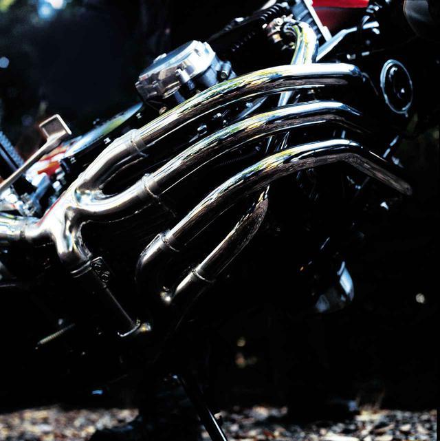 画像: 新車試乗会で特徴的なX字型エキゾーストシステムを撮影するため、2人がかりで車体を鋭角に傾けて撮影したカット。ユニークな形状は見た目の迫力と中低速域でのトルクアップに加え、脈動効果と点火順序により高回転域で排気効率を上げ、パワーアップに寄与する。