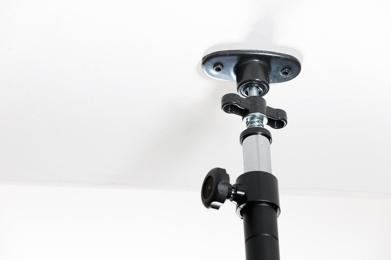 画像: 天井固定用ポールの先端には2カ所のネジ穴があり、コンクリートビスや木ネジで固定できる。 ※写真は撮影用の仮止めのためネジは入れていません。