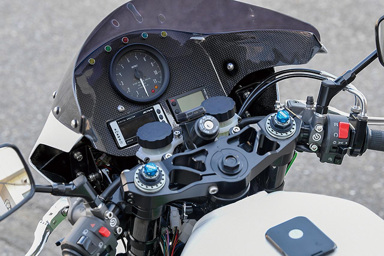 画像: ビキニカウルの内側はカーボンでメーターパネルを兼ねたインナーパネルを製作し、ULTRA回転計やアクティブ・マルチメーター、ヨシムラPRO-GRESSメーターを配置している。左右のマスターシリンダーはブレンボ・ラジアルでステムはブルドックのオリジナル、マッコイ・ブランドの可変タイプ。